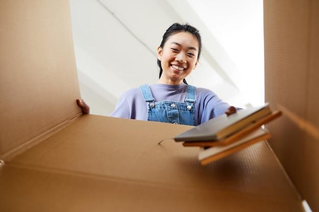 Niedrige winkelansicht an der jungen asiatischen frau, die in den karton schaut und glücklich beim packen oder auspacken für neues zuhause lächelt