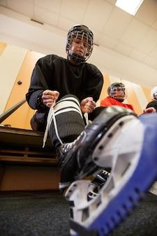 Niedrige winkelansicht bei hockeyspielerin, die ausrüstung anlegt