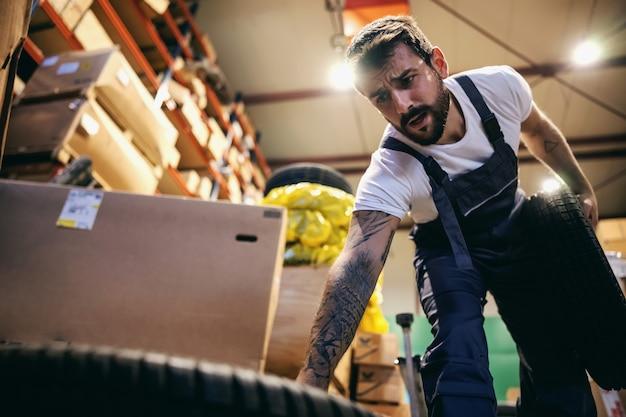 Niedrige winkelansicht des bärtigen tätowierten arbeiters, der reifen in lagerung der import- und exportfirma setzt.