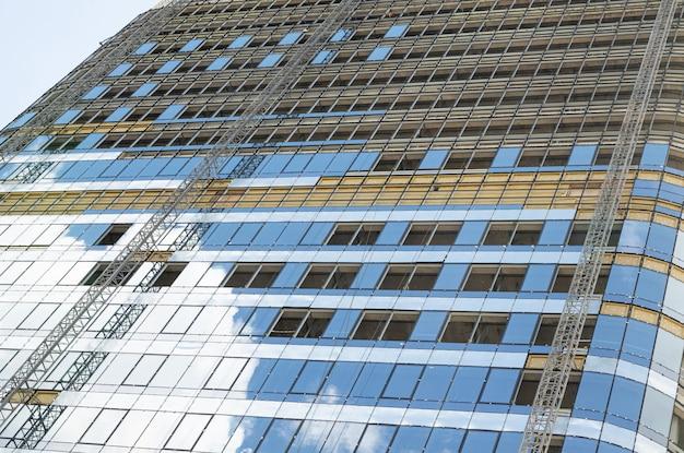Niedrige winkelansicht des hohen modernen glasgebäudes unter renovierung mit himmelsreflexion an seinen fenstern