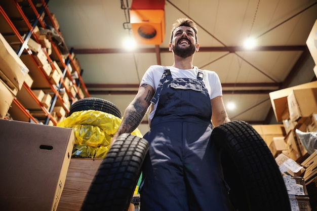 Niedrige winkelansicht des lächelnden fleißigen arbeiters in overalls, die reifen tragen und im lager in import- und exportfirma gehen.
