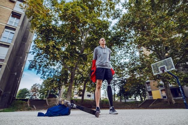 Niedrige winkelansicht des schönen kaukasischen sportlichen jungen behinderten mannes mit künstlichem bein und in sportbekleidung, die sein sweatshirt abnehmen, während sie auf basketballplatz stehen.