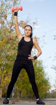 Niedrige winkelansicht einer fitten athletischen frau, die mit einer hantel trainiert, die ihren arm über ihren kopf hebt