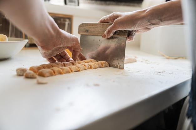 Niedrige winkelansicht einer frau, die hausgemachten süßkartoffel-gnocchi-teig schneidet