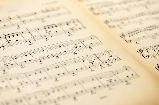 Niedrige winkelansicht einer offenen gelben gealterten vintagen musikpartitur oder noten