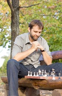 Niedrige winkelansicht eines männlichen schachspielers, der auf einer hölzernen parkbank sitzt, das schachbrett betrachtet und seine strategie ausarbeitet