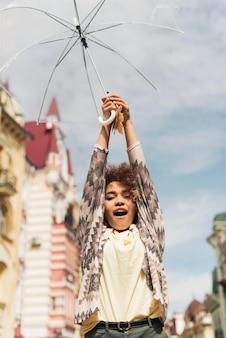 Niedrige winkelfrau, die einen transparenten regenschirm hält