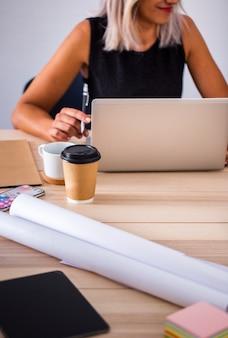 Niedrige winkelfrau im büro, das an laptop arbeitet