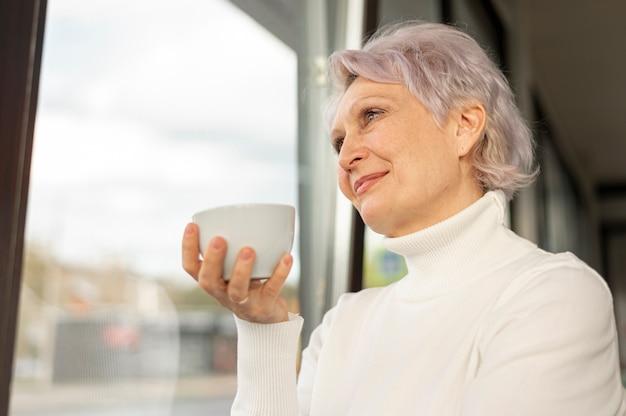 Niedrige winkelfrau mit der kaffeetasse, die auf fenster schaut