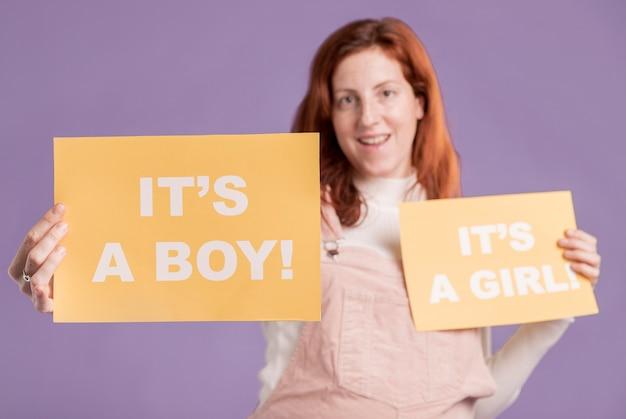 Niedrige winkelschwangere, die papier mit babygeschlecht hält
