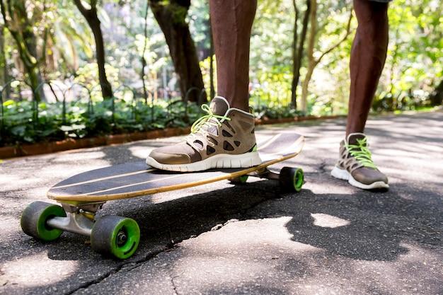 Niedrige winkelsicht der füße eines jungen männlichen skateboarders in den turnschuhen am park