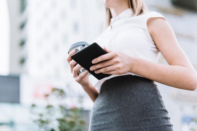 Niedrige winkelsicht der geschäftsfrau smartphone und wegwerfkaffeetasse an draußen halten
