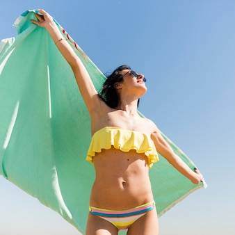 Niedrige winkelsicht der jungen frau im bikini, der in der hand das tuch steht gegen blauen himmel hält