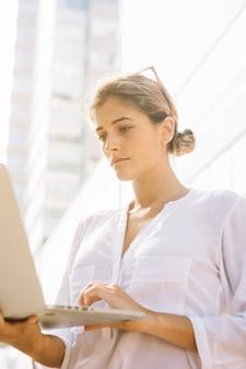 Niedrige winkelsicht der jungen geschäftsfrau, die laptop an draußen verwendet