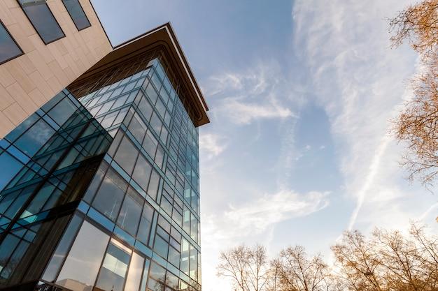 Niedrige winkelsicht der reflexion des blauen himmels in der glaswand des modernen bürogebäudewolkenkratzers im geschäftsgebiet