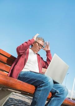 Niedrige winkelsicht des älteren mannes mit laptop auf seinem schoss gegen blauen himmel