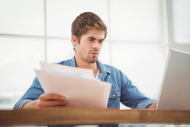 Niedrige winkelsicht des hippies dokumente beim arbeiten an laptop im büro halten