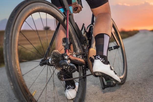 Niedrige winkelsicht des radfahrers stehend mit fahrrad bei sonnenuntergang