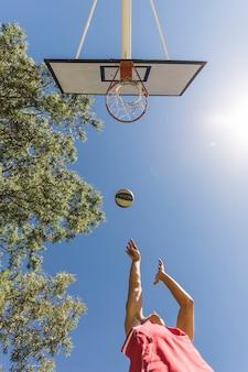 Niedrige winkelsicht des schießenbasketballspielers