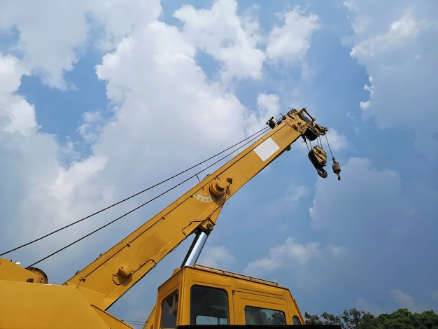 Niedrige winkelsicht des teleskopauslegers mit hebemaschine des gelben kranes an der baustelle gegen bewölkten himmel