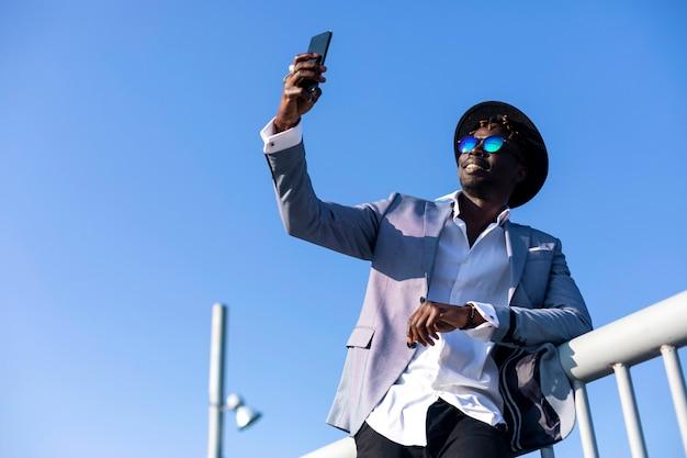 Niedrige winkelsicht des tragenden hutes und der sonnenbrille des jungen afrikanischen schwarzen mannes, die auf einem metallischen entspannenden zaun beim nehmen eines selfie sich lehnen