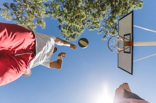 Niedrige winkelsicht des werfenden balls des basketball-spielers gegen blauen himmel