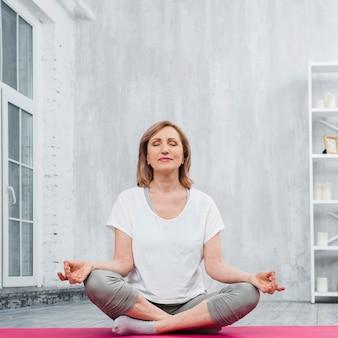 Niedrige winkelsicht einer älteren frau, die zu hause meditation tut