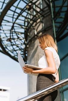 Niedrige winkelsicht einer blonden jungen geschäftsfrau, die laptop betrachtet