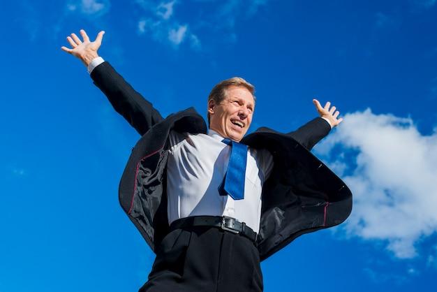 Niedrige winkelsicht eines aufgeregten geschäftsmannes, der seine arme gegen himmel anhebt