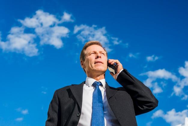 Niedrige winkelsicht eines reifen geschäftsmannes, der auf mobiltelefon gegen himmel spricht