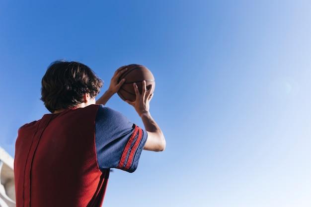 Niedrige winkelsicht eines teenagers, der basketball gegen blauen himmel hält