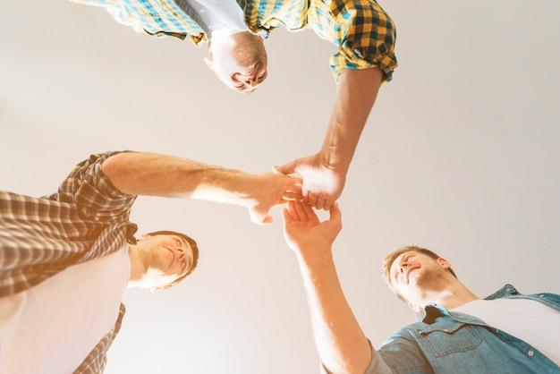 Niedrige winkelsicht von den männlichen freunden, die miteinander hoch fünf geben