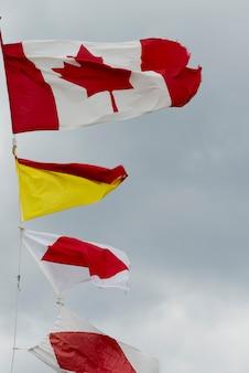 Niedrige winkelsicht von flatternden flaggen am hummer-bucht-hauptleuchtturm, gros morne national park, newfou
