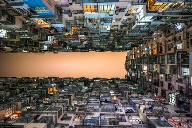 Niedrige winkelsicht von gedrängten wohntürmen in einer alten gemeinschaft in der steinbruch-bucht, hong kong. szenerie von überfüllten, engen wohnungen, ein phänomen von hoher wohndichte und blues.