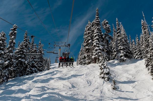 Niedrige winkelsicht von skifahrern auf skiliften, symphonie-amphitheater, pfeifer, britisch-columbia, kanada