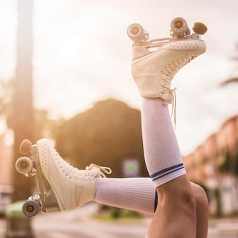 Niedrige winkelsicht von tragenden weinleserollschuhen des beines der frau