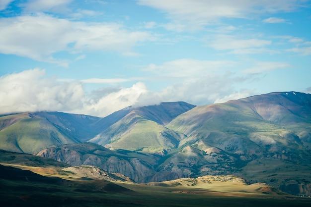 Niedrige wolken über schönen grünen bergen. fantastische hochlandlandschaft mit großen bergen unter niedrigen wolken. bunte alpine landschaft mit riesigen grünen bergen im sonnenlicht unter blauem bewölktem himmel.