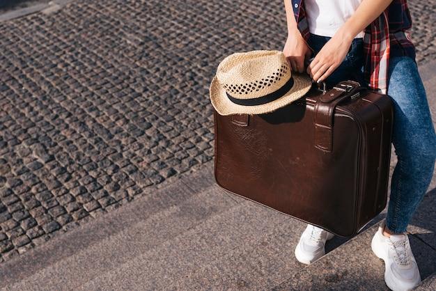 Niedriger abschnitt der frau braune gepäcktasche mit dem hut tragend, der auf treppenhaus steht