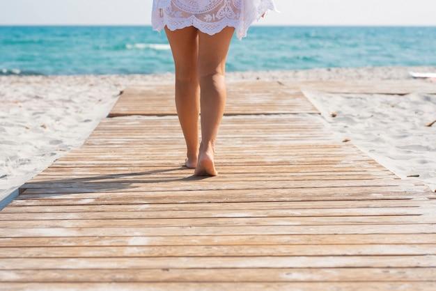 Niedriger abschnitt der frau, die auf holzbrett inmitten von sand geht, der in richtung meerwasser führt. frau zu fuß in richtung meer durch hölzernen beplankten fußweg entlang des sandstrandes