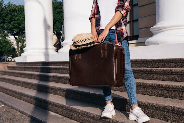 Niedriger abschnitt der frau die gepäcktasche halten, die auf treppenhaus am freien steht