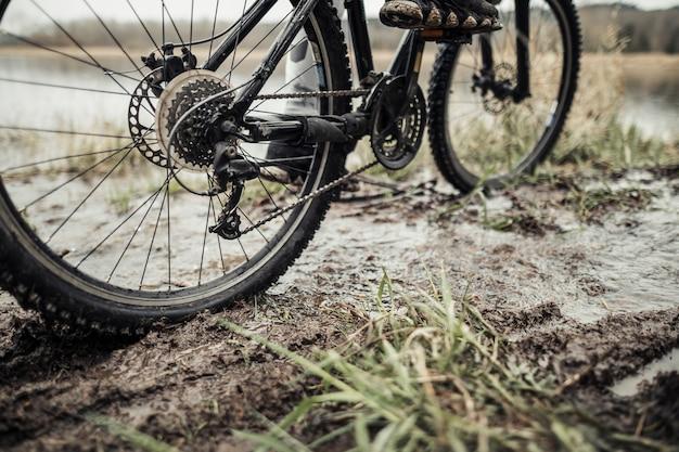 Niedriger abschnitt der füße des radfahrers auf fahrrad im schlamm
