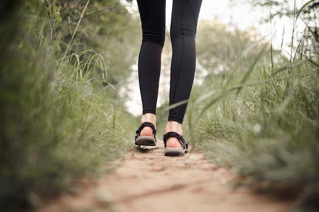 Niedriger abschnitt der füße des weiblichen wanderers, der auf spur geht