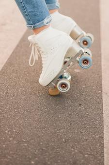 Niedriger abschnitt des fußes der frau tragenden weißen rollschuh, der auf straße balanciert