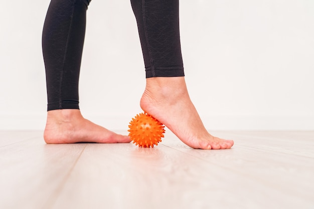 Niedriger abschnitt des mädchens trainierend mit druckball im krankenhaus. massageball unter dem fuß.