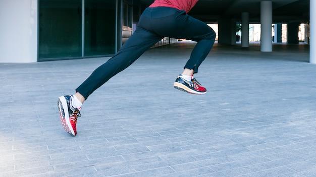 Niedriger abschnitt des männlichen athleten laufend und an draußen springend