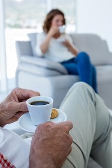 Niedriger abschnitt des mannes, der kaffee mit frau zu hause trinkt
