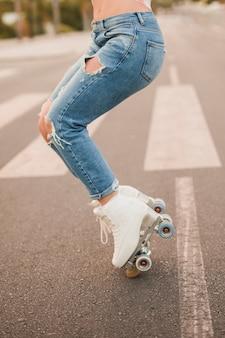 Niedriger abschnitt des tragenden weißen rollschuhs der frau, der auf straße balanciert
