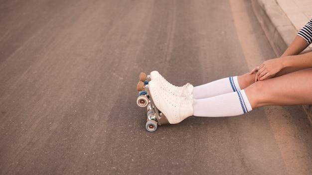Niedriger abschnitt des tragenden weißen rollschuhs der frau, der auf straße sitzt
