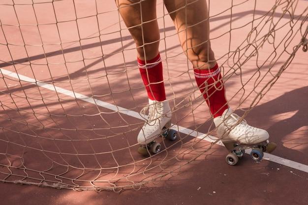 Niedriger abschnitt des tragenden weißen rollschuhs der frau, der nahe dem fußballzielnetz steht