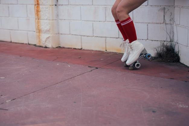 Niedriger abschnitt des weiblichen schlittschuhläufers balancierend auf rollschuh